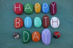Funny happy birthday postcard idea with colored stone letters and ornamental stone objects over green sand