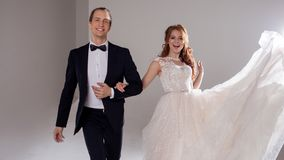 Funny and happy bride and groom, dance and jump with happiness, married. Studio portrait, light background. Boyfriend and girlfriend, costume and wedding dress Stock Photo