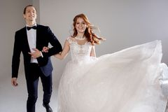 Funny and happy bride and groom, dance and jump with happiness, married. Studio portrait, light background. Boyfriend and girlfriend, costume and wedding dress Royalty Free Stock Image