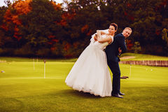 Funny happy bride and groom on green field Royalty Free Stock Images