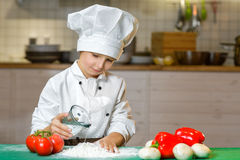 Funny happy chef boy cooking at restaurant kitchen Royalty Free Stock Image