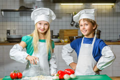 Funny happy chef boy and girl cooking at Stock Image