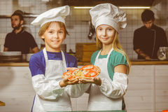 Funny happy chef boy and girl cooking at Royalty Free Stock Image