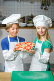 Funny happy chef boy and girl cooking at Royalty Free Stock Photography