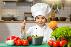 Funny happy chef boy holding bell pepper or Royalty Free Stock Photos
