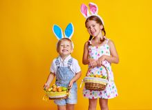 Funny happy child boy with easter eggs and bunny ears on yellow royalty free stock photos