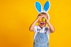 Funny happy child boy with easter eggs and bunny ears on yellow stock image