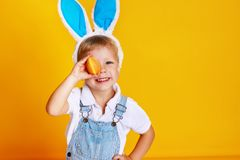 Funny happy child boy with easter eggs and bunny ears on yellow stock photography