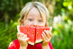 Funny happy child eating watermelon outdoors. Making a smile stock images