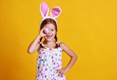 Funny happy child girl with easter eggs and bunny ears on yellow royalty free stock photography