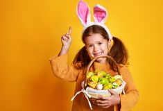 Funny happy child girl with easter eggs on yellow royalty free stock photography