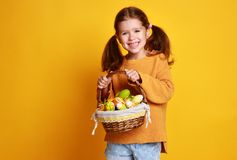 Funny happy child girl with easter eggs on yellow stock photography