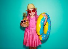 Funny happy child girl in summer pink dress with pineapple and swimming circle on blue background stock photo