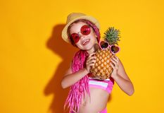 Funny happy child girl in swimsuit, pink glasses and hat with pineapple is laughing on yellow background royalty free stock photos