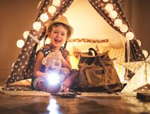 Funny child girl tourist with flashlight and world map and backp Stock Photos
