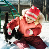 Funny happy child playing with cat. Royalty Free Stock Photo