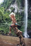 Funny child sit on snag under waterfall in tropical jungle royalty free stock photography