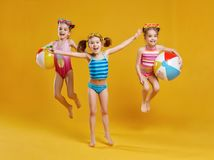 Funny funny happy children  jumping in swimsuit  jumping  on col. Funny funny happy children  jumping in swimsuit and swimming glasses jumping on colored Royalty Free Stock Images