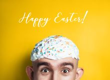 Emotional portrait of surprised bald man with easter cake on his head. Funny Easter concept. Funny Happy Easter concept. Emotional portrait of surprised bald stock photography