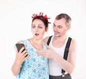 Funny happy family couple using smartphone Royalty Free Stock Photos