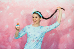 Funny happy girl with birthday cupcake. Over pink background, celebrating anniversary, holiday concept Stock Images