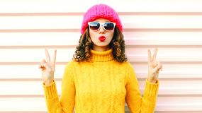 Funny happy girl blowing red lips makes air kiss wearing colorful knitted yellow sweater hat stock image