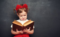 Funny happy  girl schoolgirl with book from blackboard Royalty Free Stock Photo