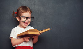 Funny happy  girl schoolgirl with book from blackboard Stock Images