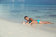 Funny happy joyful little girl lying, playing and relaxing in the ocean at early morning Stock Photo