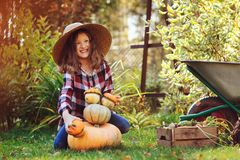 Funny happy kid girl playing with pumpkins and building `snowman` in autumn garden Stock Image