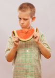 Funny and happy little boy eating watermelon. Stock Photo