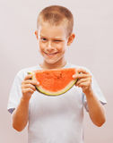 Funny and happy little boy eating watermelon. Stock Photos