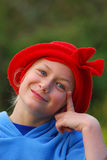 Happy little girl portrait. Outdoor portrait of a cute little Caucasian girl child with funny happy smiling facial expression wearing a red winter hat on her stock photo