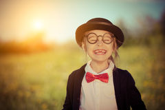 Funny happy little girl in bow tie and bowler hat. Stock Photo
