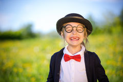 Funny happy little girl in bow tie and bowler hat. Stock Images