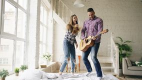 Funny happy and loving couple dance on bed singing with tv controller and playing guitar. Man and woman have fun during. Funny happy and loving couple dance on stock image