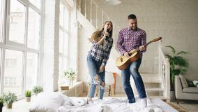 Funny happy and loving couple dance on bed singing with tv controller and playing guitar. Man and woman have fun during. Funny happy and loving couple dance on stock photo