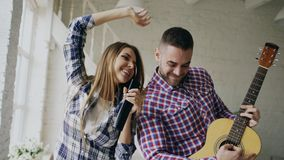 Funny happy and loving couple dancing and playing guitar. Man and woman have fun during their holiday at home. Funny happy and loving couple dance on bed singing Stock Photo