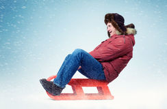 Funny happy man in winter clothes fly on a sled in the snow Stock Photo