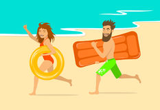 Funny happy man and woman running on a beach with inflatable swimming mattress and ring Stock Photo