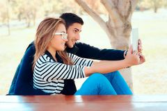 Cute Couple Using PC Tablet Outdoors in Nature. Funny happy smiling girlfriend and boyfriend with notepad in the park Royalty Free Stock Photo