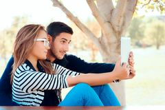 Cute Couple Using PC Tablet Outdoors in Nature. Funny happy smiling girlfriend and boyfriend with notepad in the park Royalty Free Stock Image