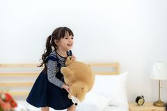 Funny happy toddler girl jumping and playing with her toy teddy bear in bed. Kids play at home. White nursery. Child in sunny bedroom stock image
