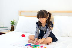 Funny happy toddler girl reading a book and playing with her toy teddy bear in bed. Kids play at home. White nursery. Royalty Free Stock Photo