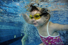 Funny happy toddler girl swimming underwater in a pool with lots of air bubbles Stock Photos