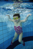 Funny happy toddler girl swimming underwater in a pool with lots of air bubbles Royalty Free Stock Photos