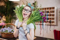 Funny happy woman florist holding two bunches of tulips Royalty Free Stock Images