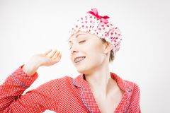 Funny woman wearing pajamas and bathing cap Stock Photos