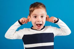 Funny happy young boy in sweater showing grimace at camera stock photography