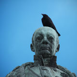 Funny Hat. A bird on the head of a statue Stock Photography